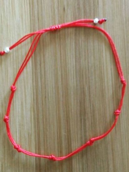 Una pulsera de cordón rojo con siete nudos es un amuleto popular para protegerte<br />