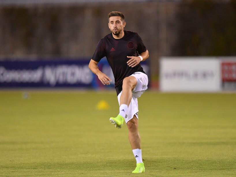 Héctor Herrera con playera negra y un pie alzado