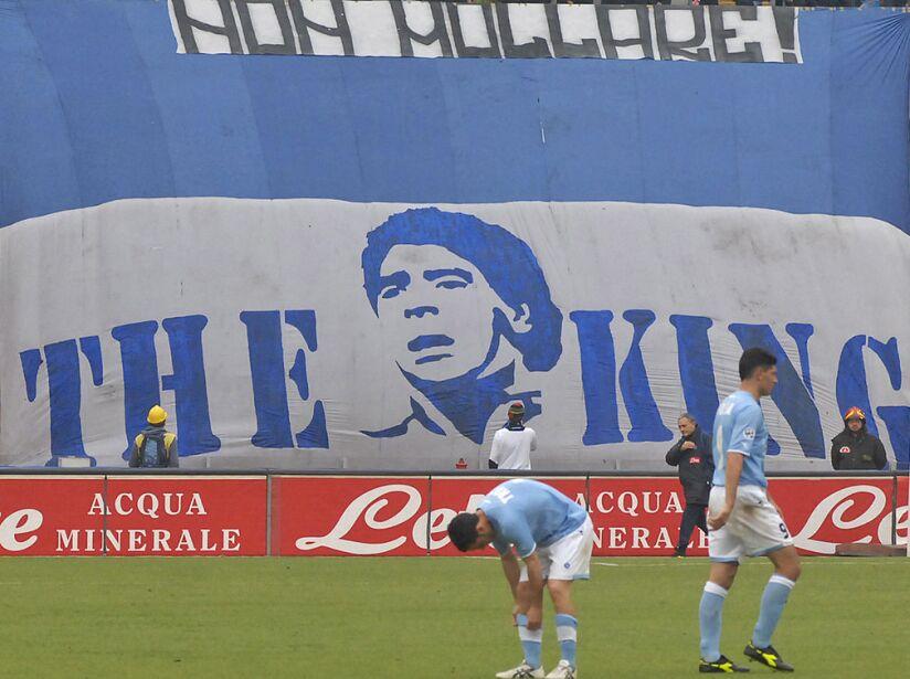 Football player trains past a giant bann