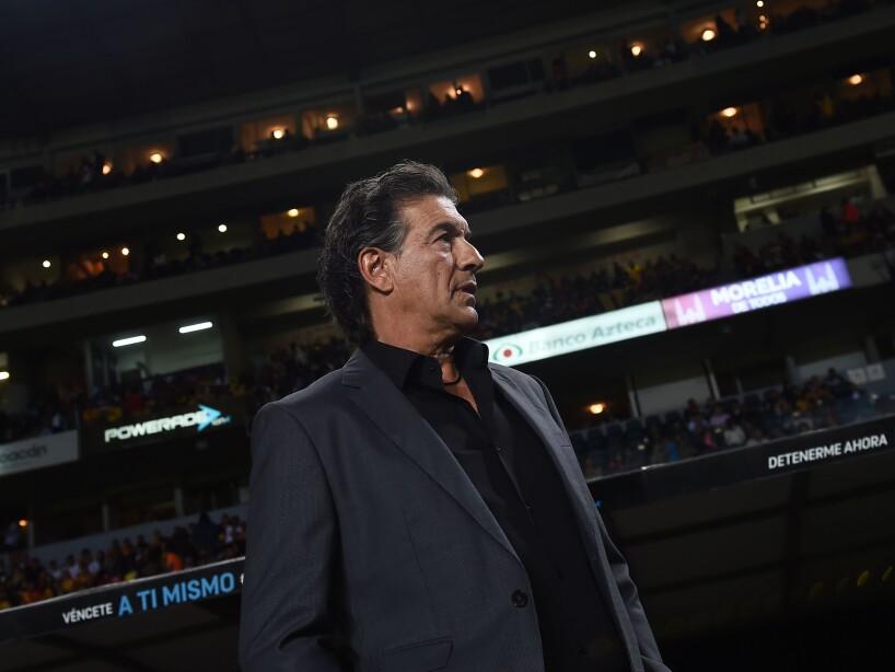 Ruben Omar Romano mirando a la tribuna de traje