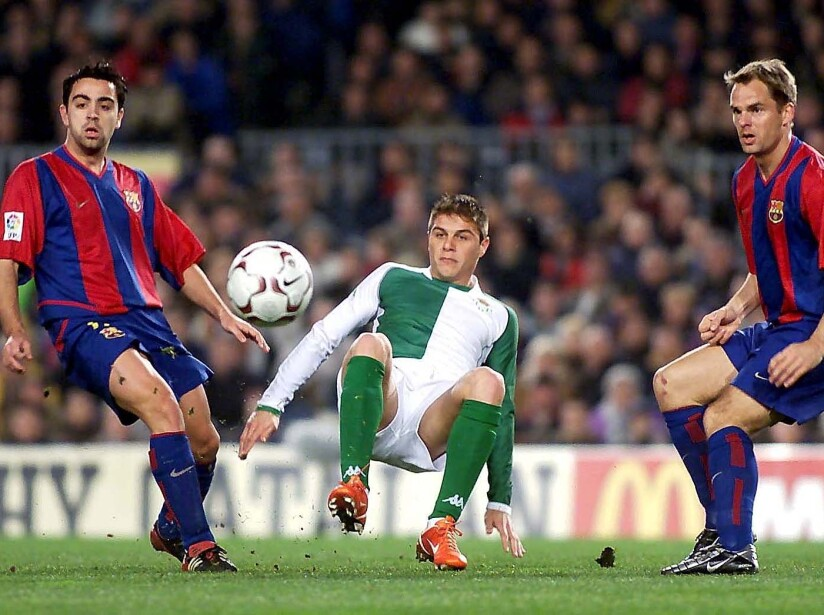 Joaquin of Betis battles with Xavi (L) and Frank de Boer