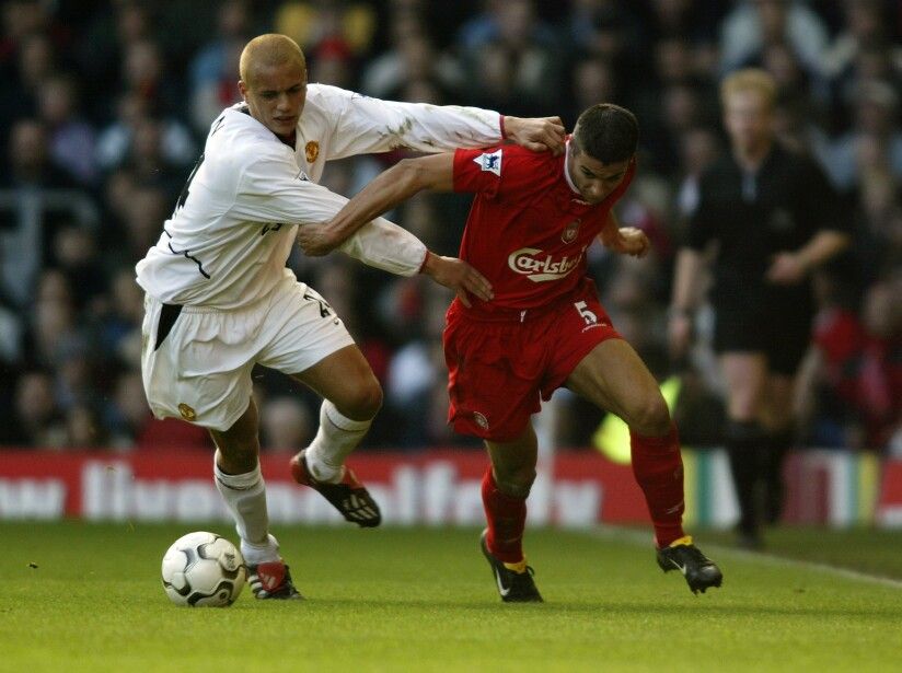 Milan Baros of Liverpool and Wes Brown of Manchester United