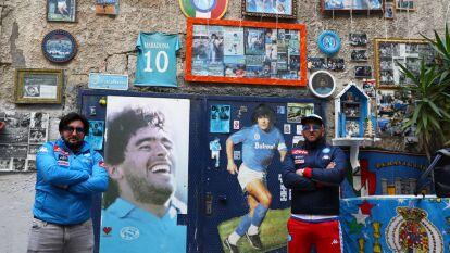 Dos fans del Napoli posan fuera de un local que muestra la historia de Diego Armando Maradona, el jugador más grande que ha tenido el equipo del sur de Italia.